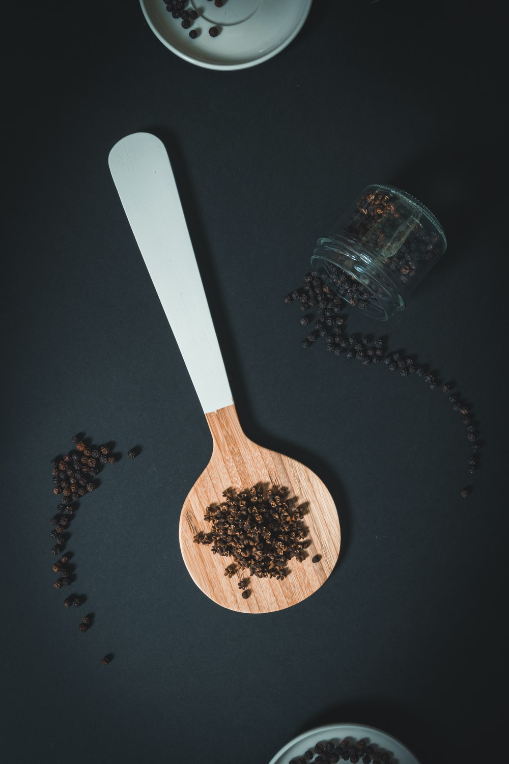 white and brown wooden spoon with pepper
