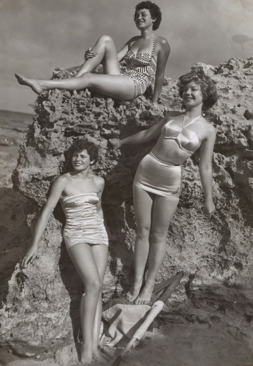 grayscale photo of three women standing and sitting on rocks