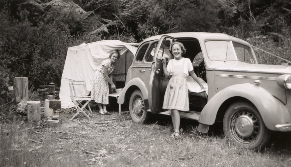 grayscale photo of girl beside car