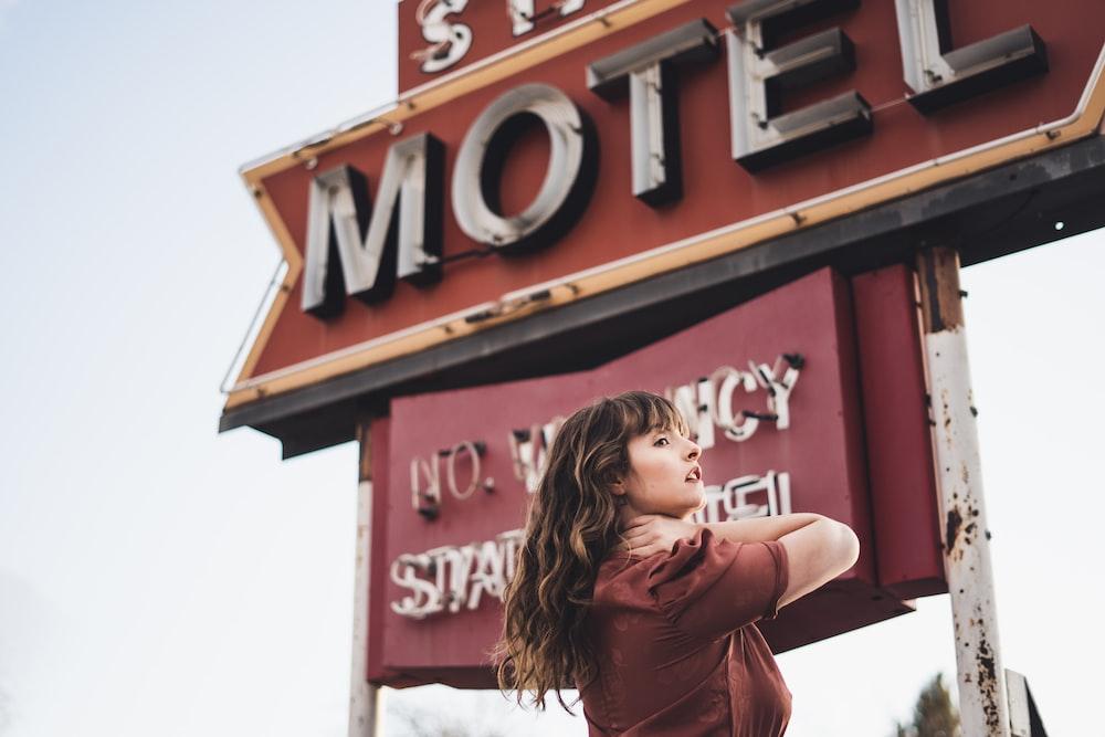 woman standing near motel sign