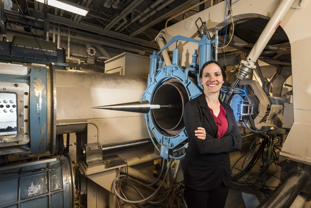 woman in black jacket beside blue industrial machine
