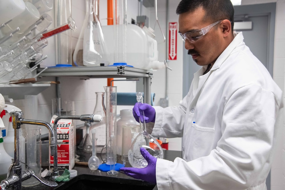 man mixing a flask inside a laboratory