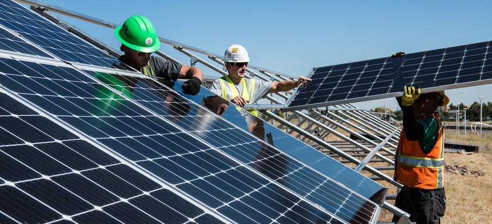 men holding solar panels