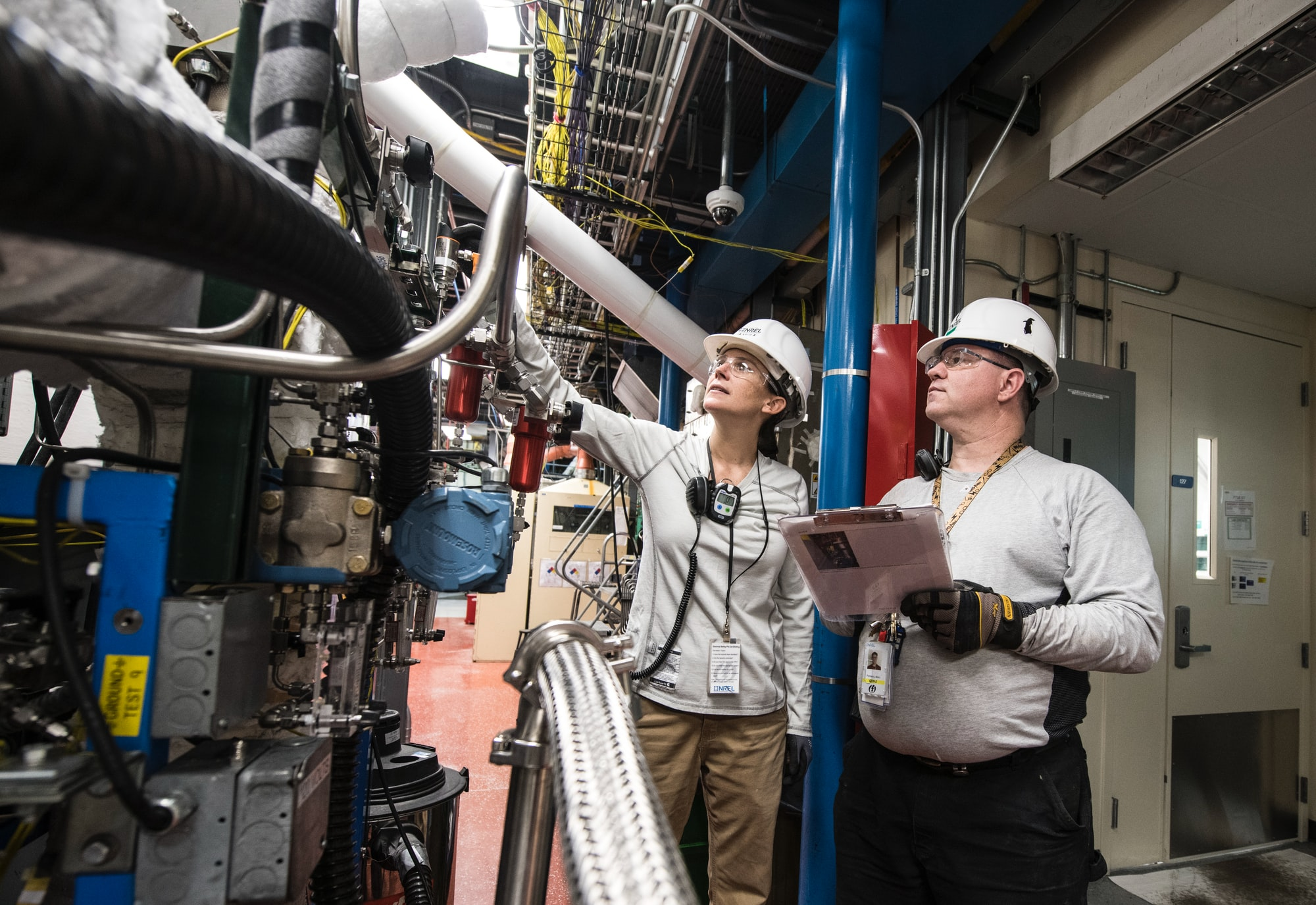 NREL Thermochemical Process/ Control Engineer and Research Technician work during a 48 hour Hot Test in Thermochemical User Facility Pilot Plant in the Field Test Laboratory Building (FTLB).