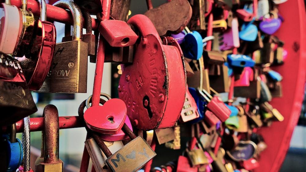 metal padlocks on red fence