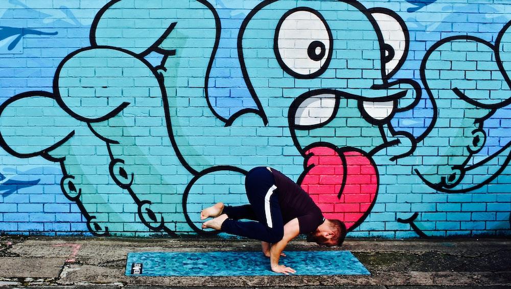 man wearing black t-shirt doing stunt near graffiti wall