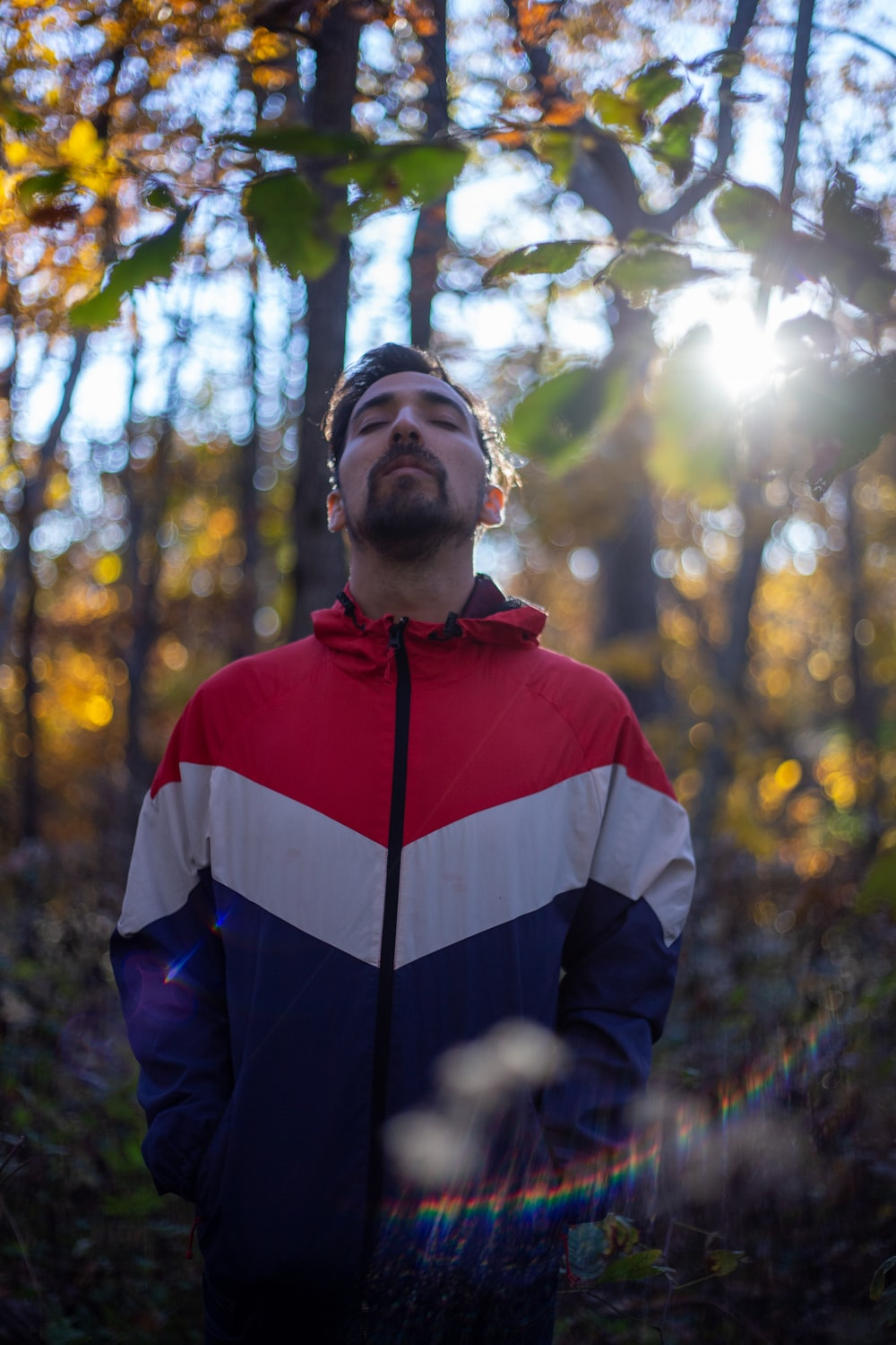 man in red, white, and blue zip-up jacket standing in forest