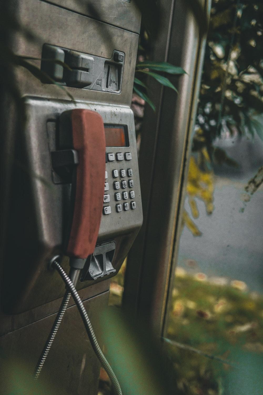 gray payphone beside tree