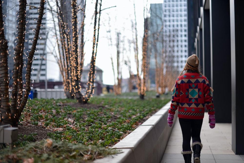 woman walking beside bare trees during daytime