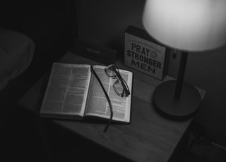 grayscale photography of eyeglasses on open book near table lamp