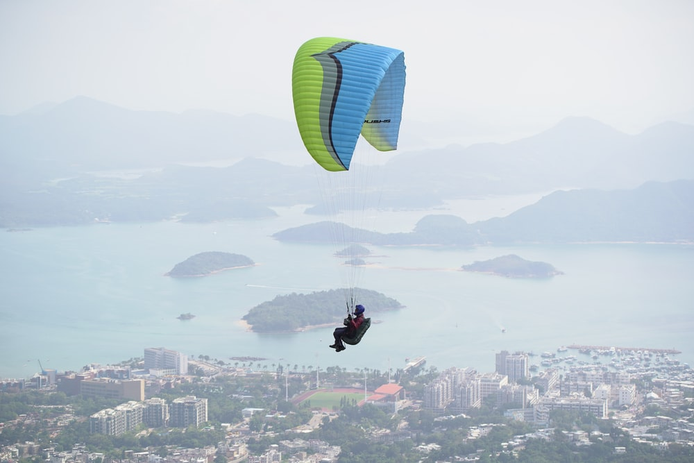 man on blue and green parachute