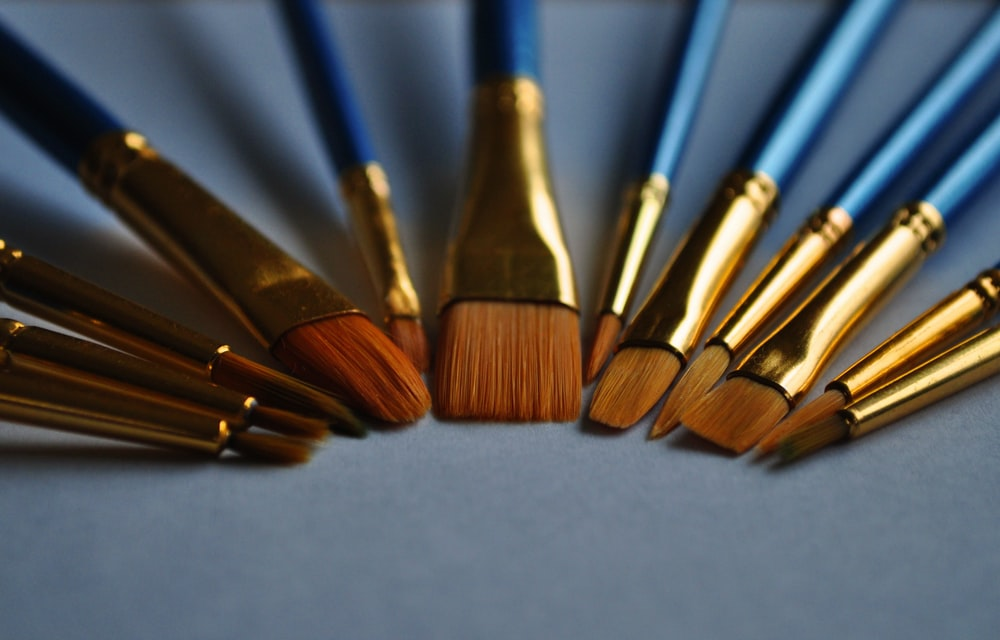 macro photography of blue and gold makeup brush set