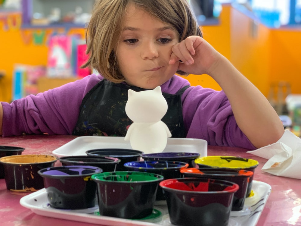 child sitting in front of table with white animal toy and containers of paints