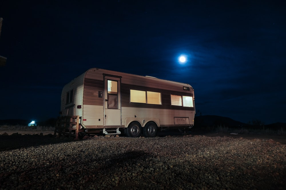 white and gray camper trailer on field during night time