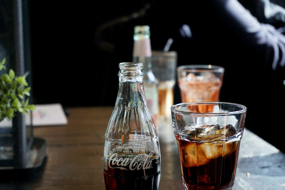 Coca-Cola glass bottle beside a glass of soda with ice cubes photo – Free  Drink Image on Unsplash