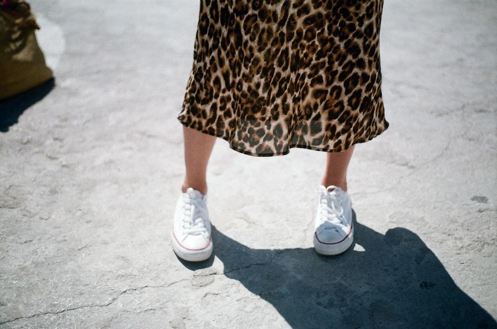 woman wearing white low-top sneakers