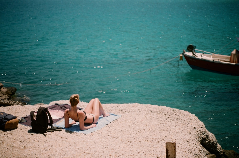 woman lying on cliff overlooking body of water