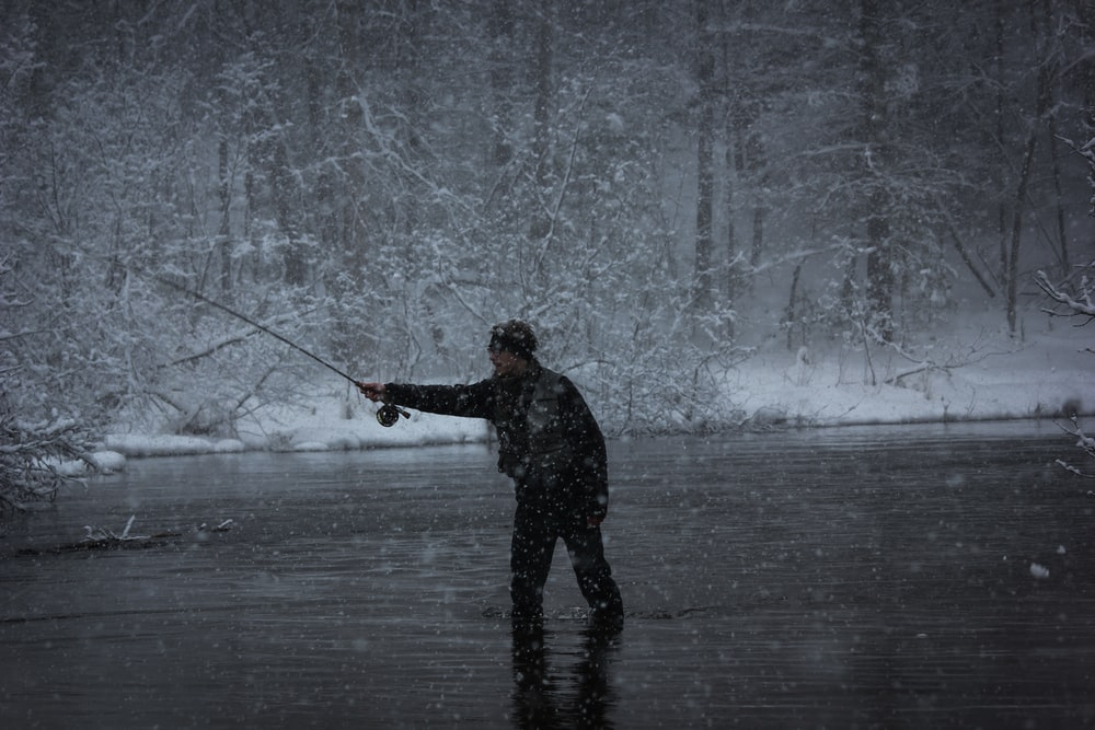 grayscale photography of man fishing in body of water while snowing