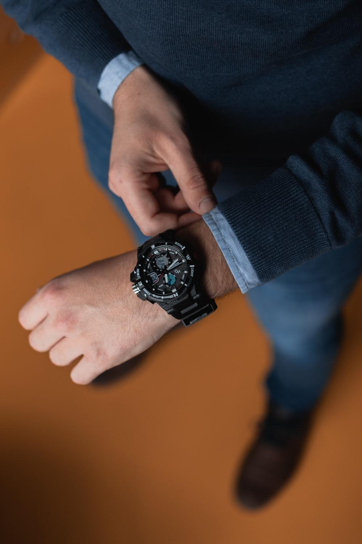 person wearing round black analog digital watch