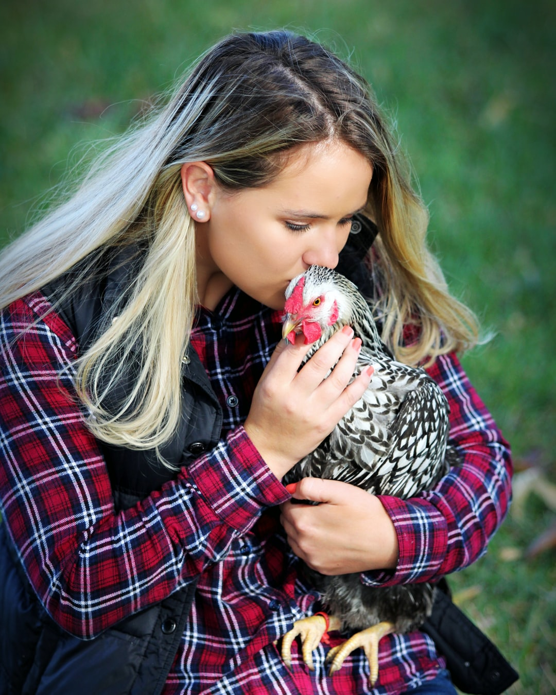 A girl kisses a chicken in the grass wearing a flannel shirt.
