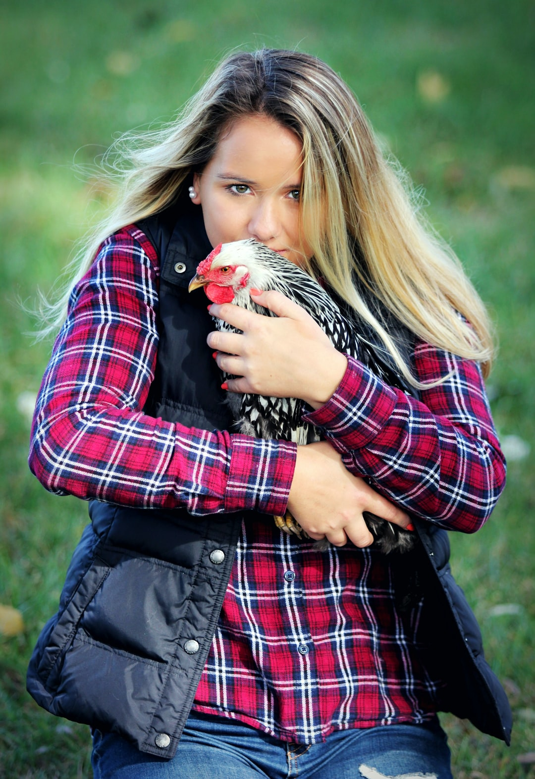 A girl kisses a chicken in the grass while wearing a red flannel shirt and blue jeans.