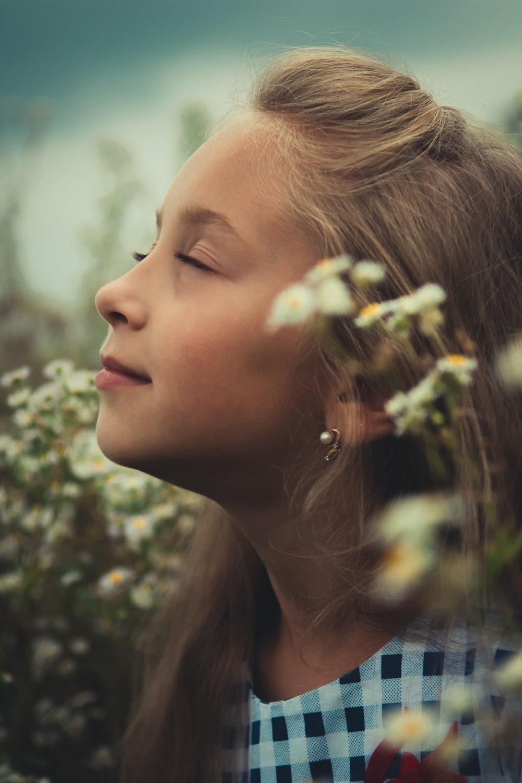 girl standing near white petaled flowers