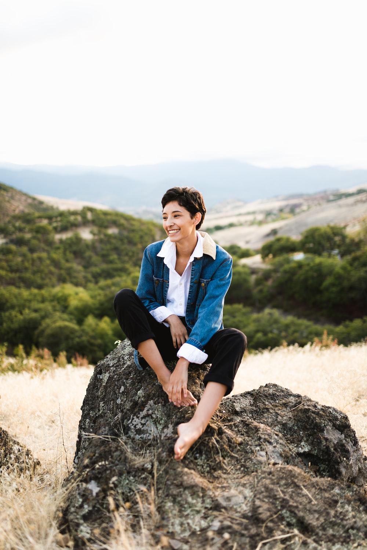 woman sitting on rock