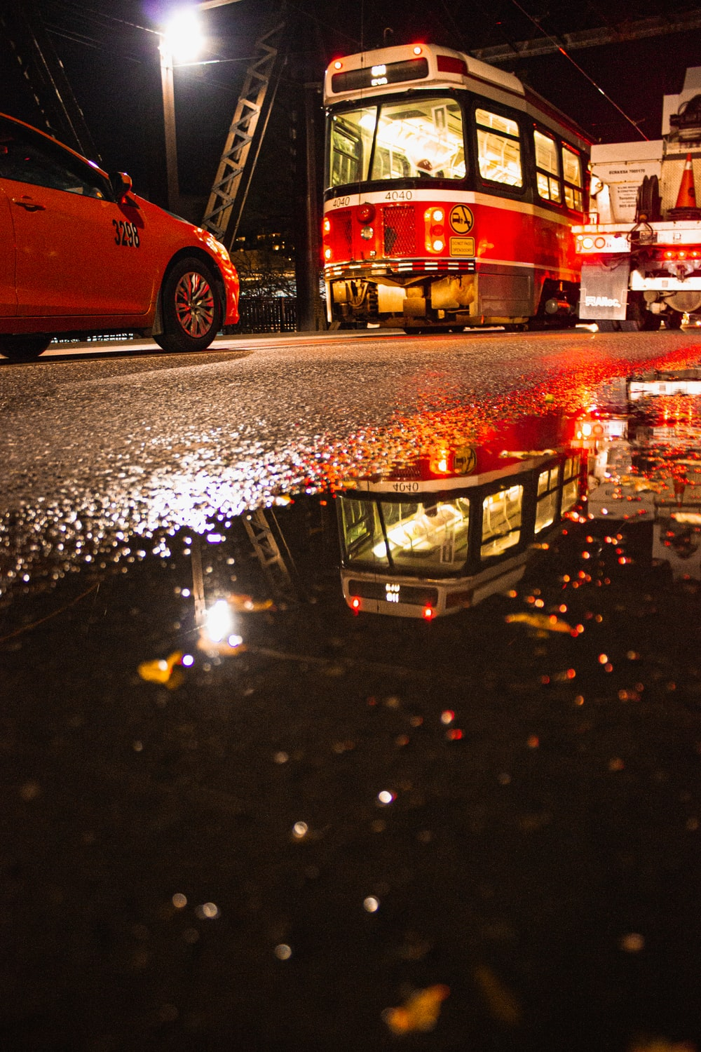 red vehicle passing near water puddle on road at night
