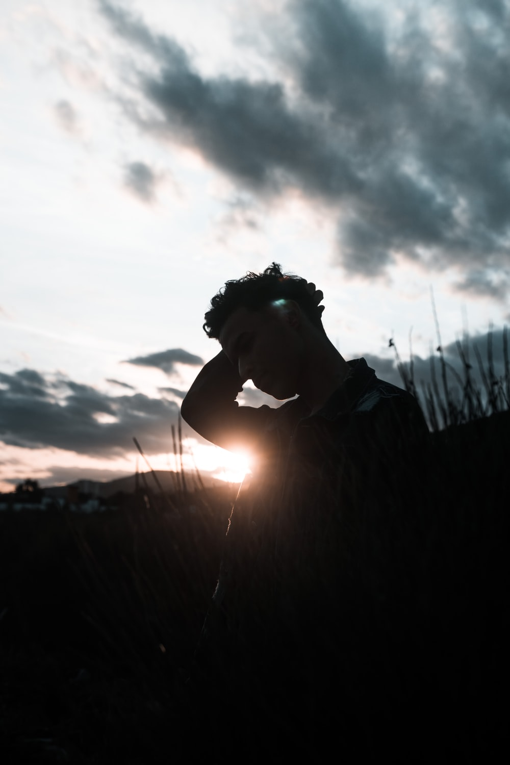 silhouette photography of man standing in grass during dawn