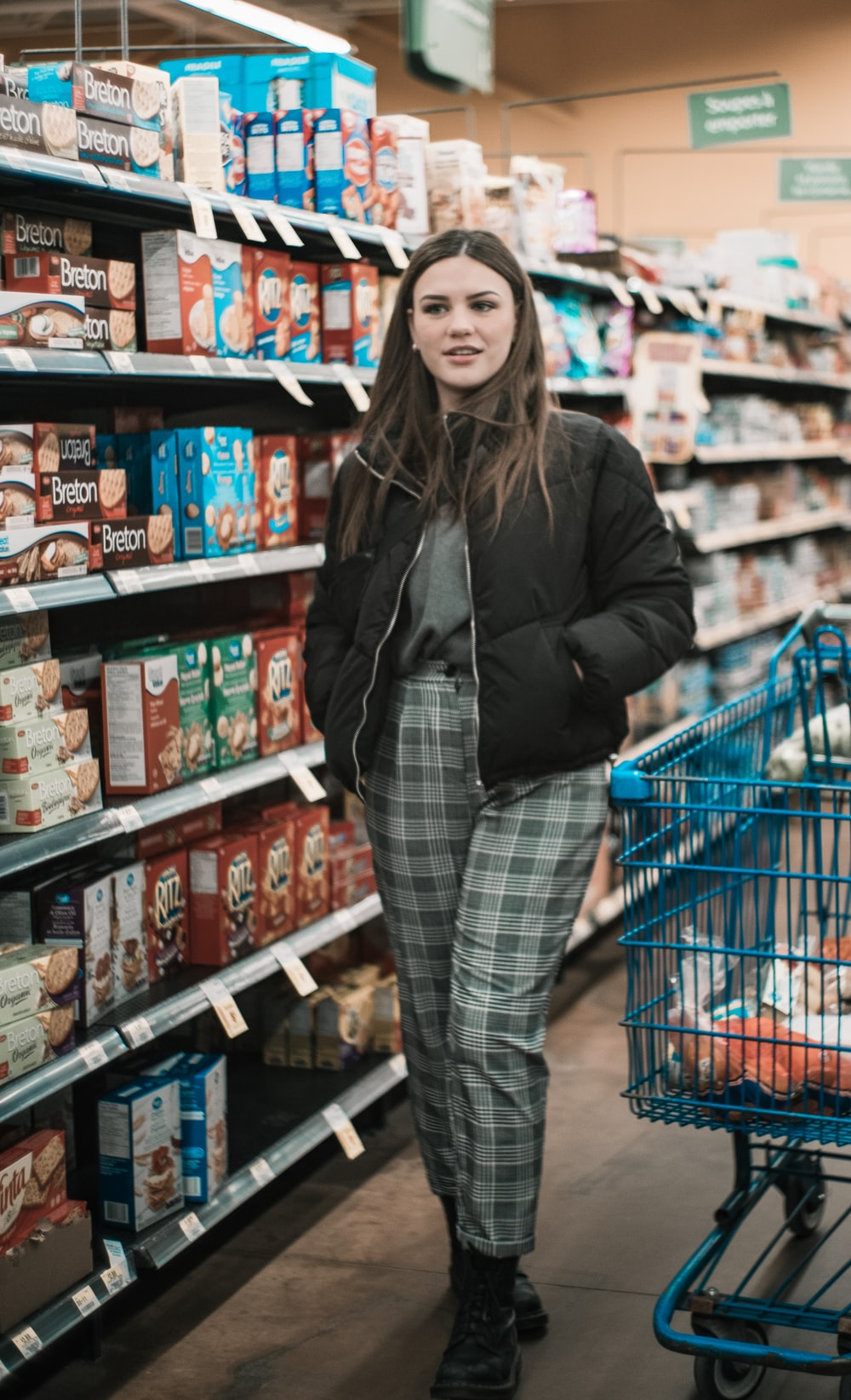 woman standing near shopping cart and groceries inside warehouse