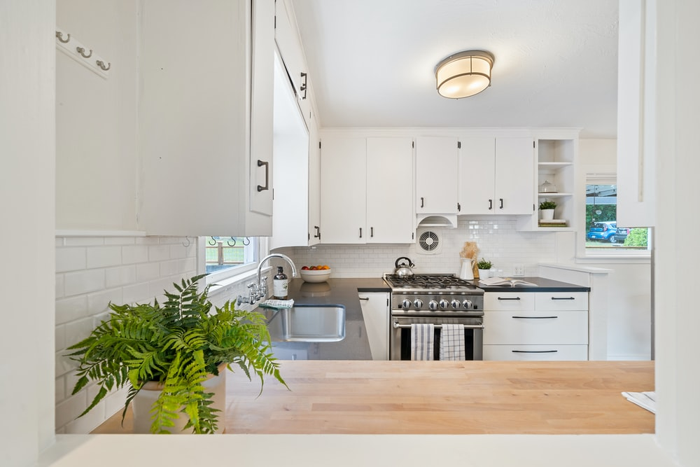 white wooden kitchen cupboards and gray gas stove