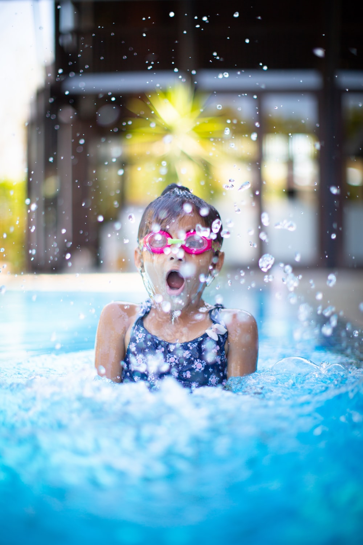 girl swims on swimming pool