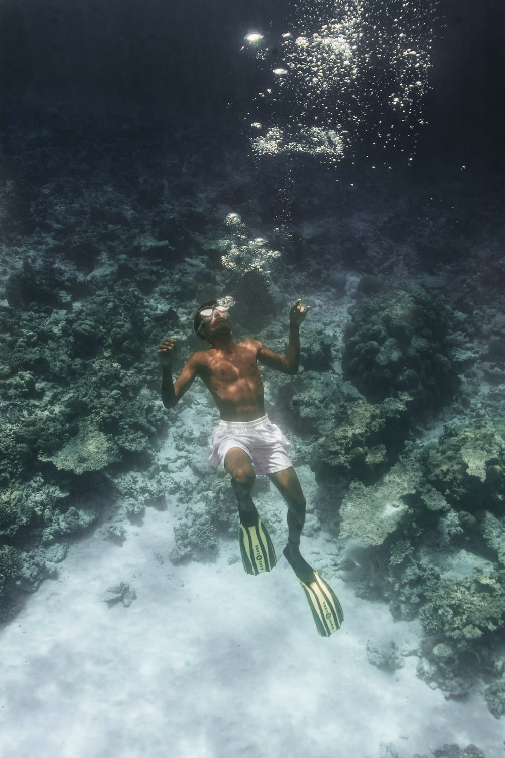 man with swimming flippers diving underwater