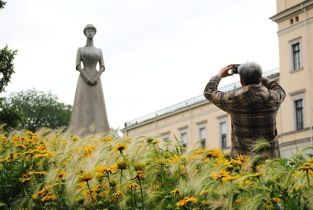 man standing while taking picture of woman statue