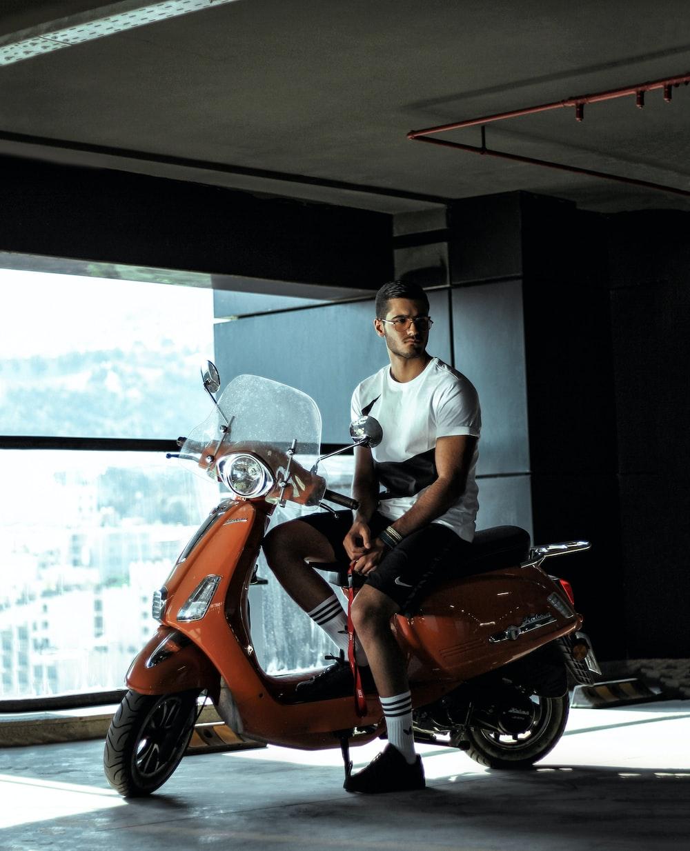 man wearing white crew-neck t-shirt sitting on orange motor scooter