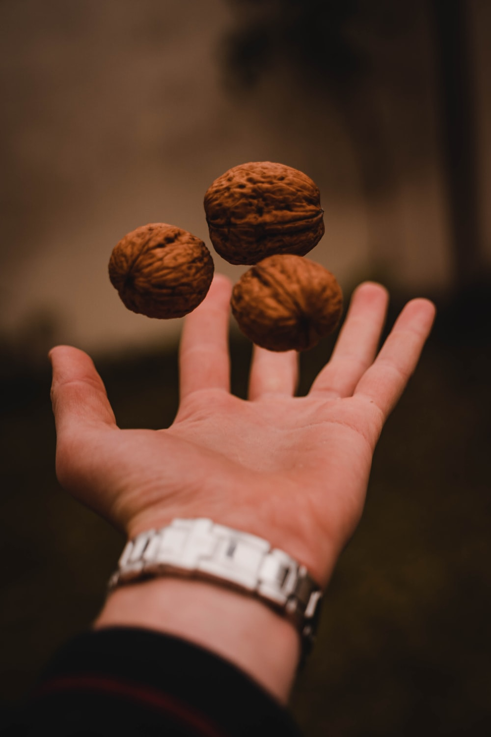 person throwing three walnuts