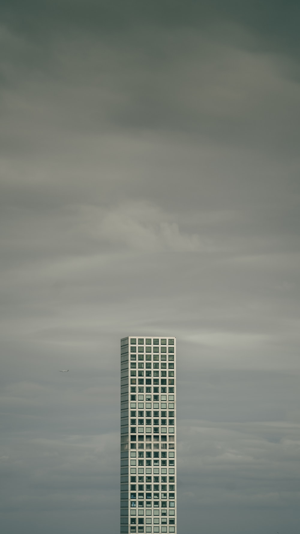 gray high-rise building under cloudy sky during daytime