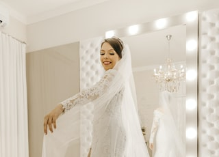 woman wearing white wedding dress in front of mirror