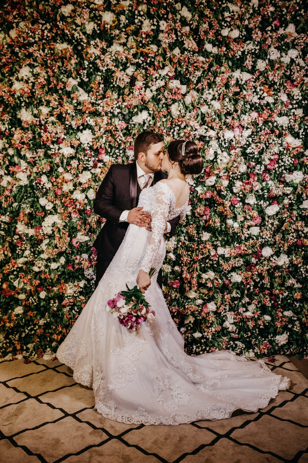 wedding couple kissing with red and white flowers background