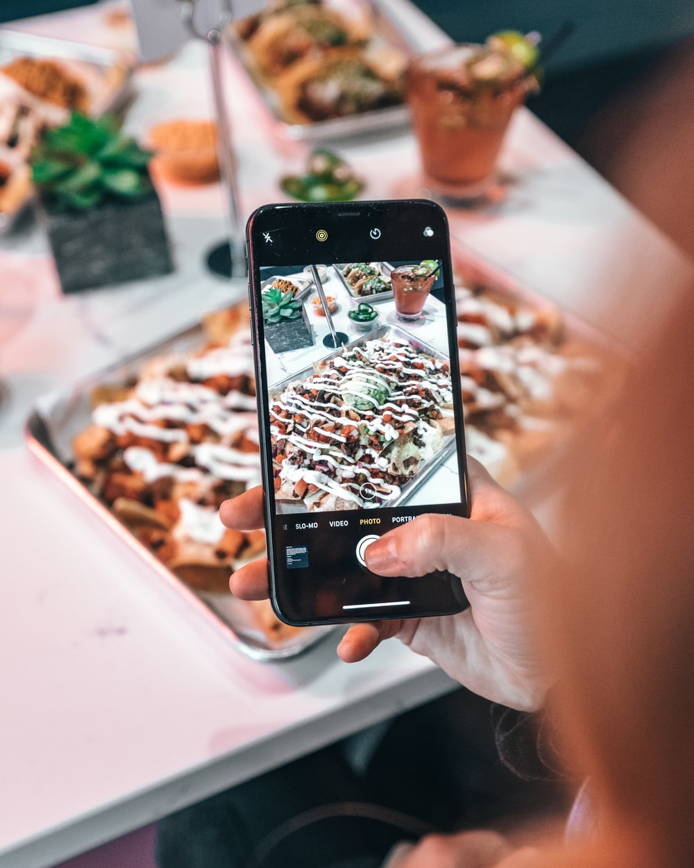 person taking picture of food with black smartphone