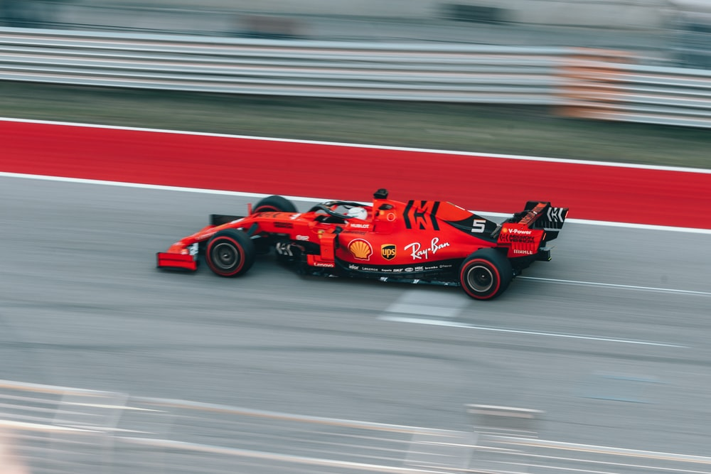 selective focus photography of red Formula 1 on track