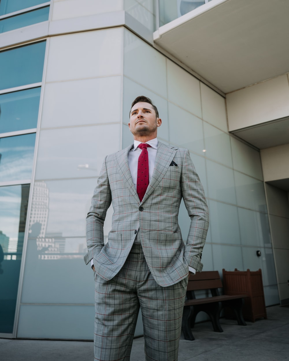 man in gray notched lapel suit jacket standing in front of building