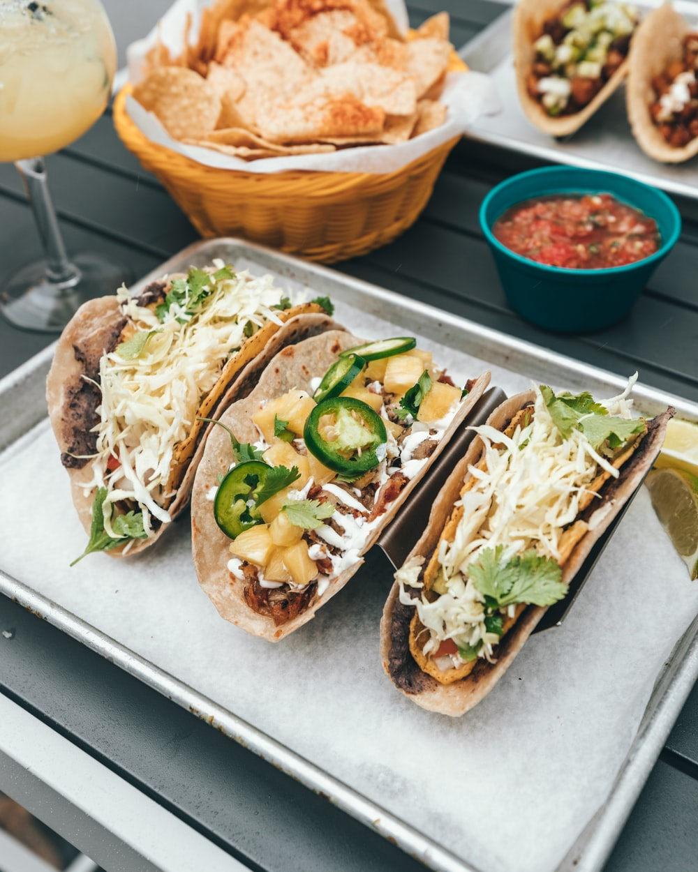 three fresh tacos on gray tray