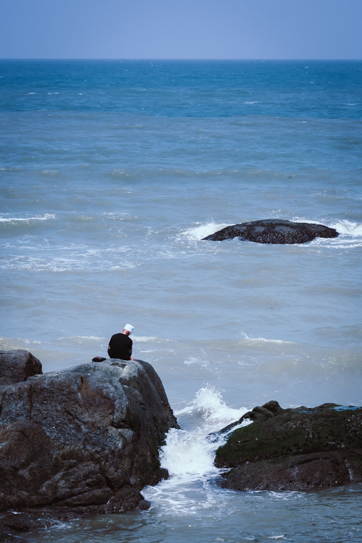 man sitting on rock on sea during daytime