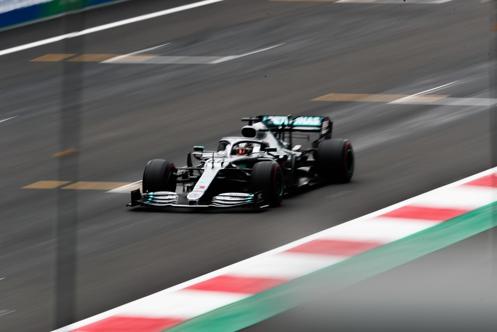 white and black F1 car on race track