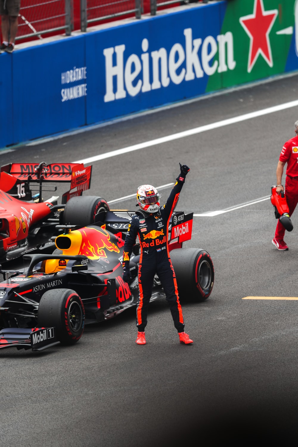 man raising his left hand in front of race car