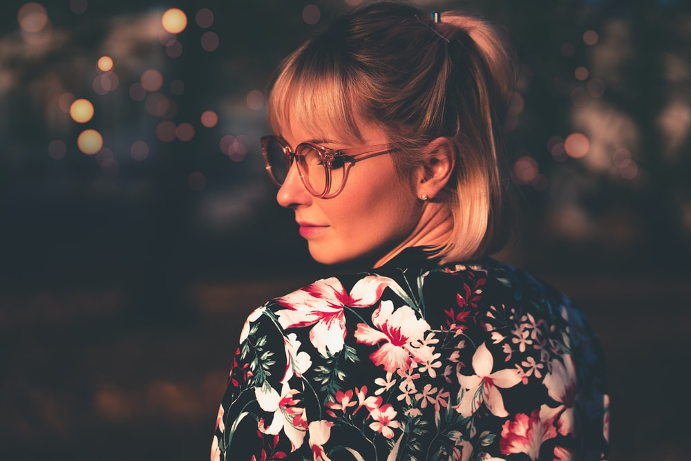 woman wearing multicolored floral top looking side