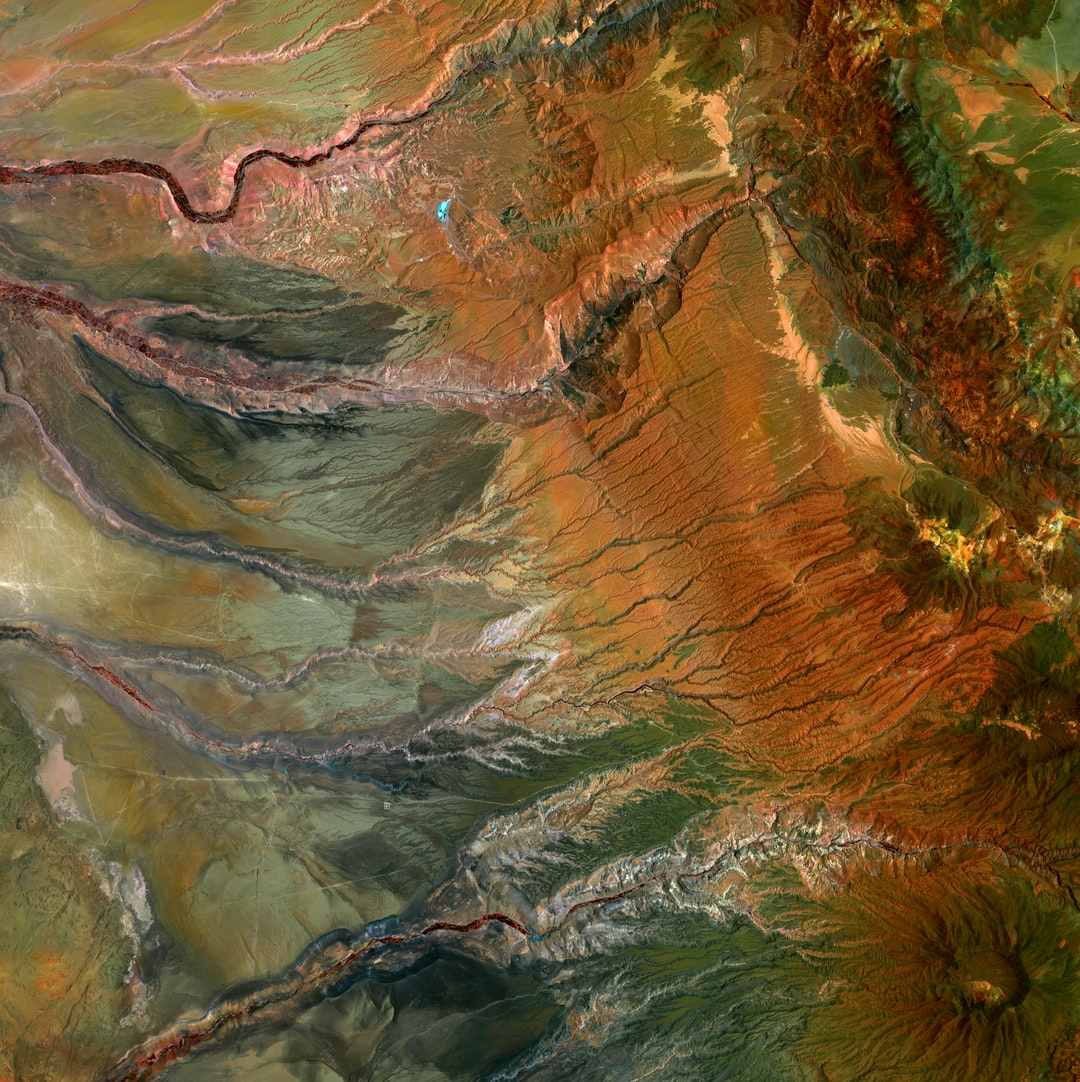 These orange shades and ragged shapes give an impression of moodiness. The jagged scars are extensive valleys carved by water flowing from the Andes Mountains in northern Chile. The crater in the lower right is the volcano Cerro Guachiscota.