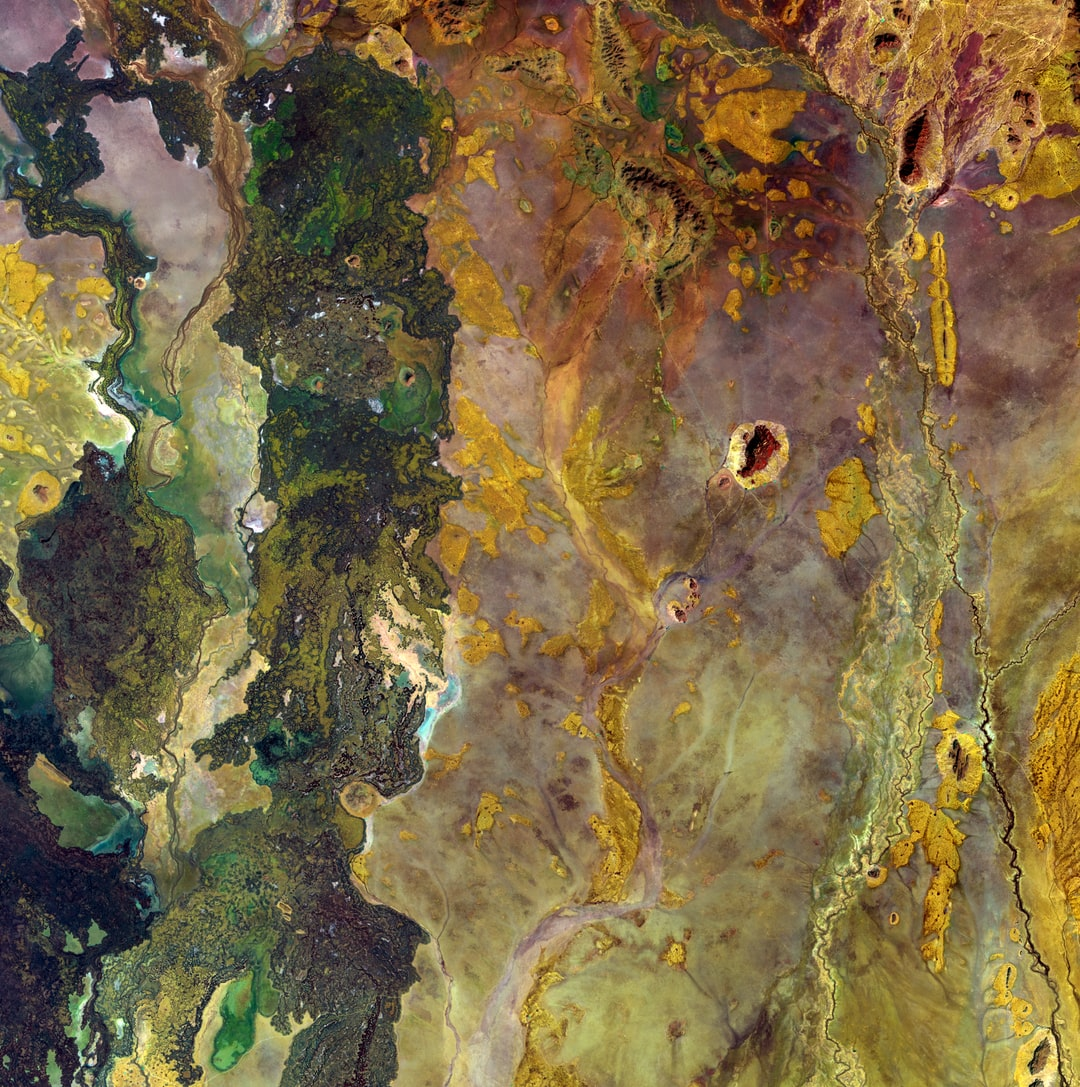 Green shades seem to be bubbling up like a lava lamp on the left side of this image from northeastern Kenya. The right side is like rusted metal. The dark green is the result of geologically recent lava flows, and the other colors are different types of soils. Even with few defined shapes, the piece has a strange beauty.