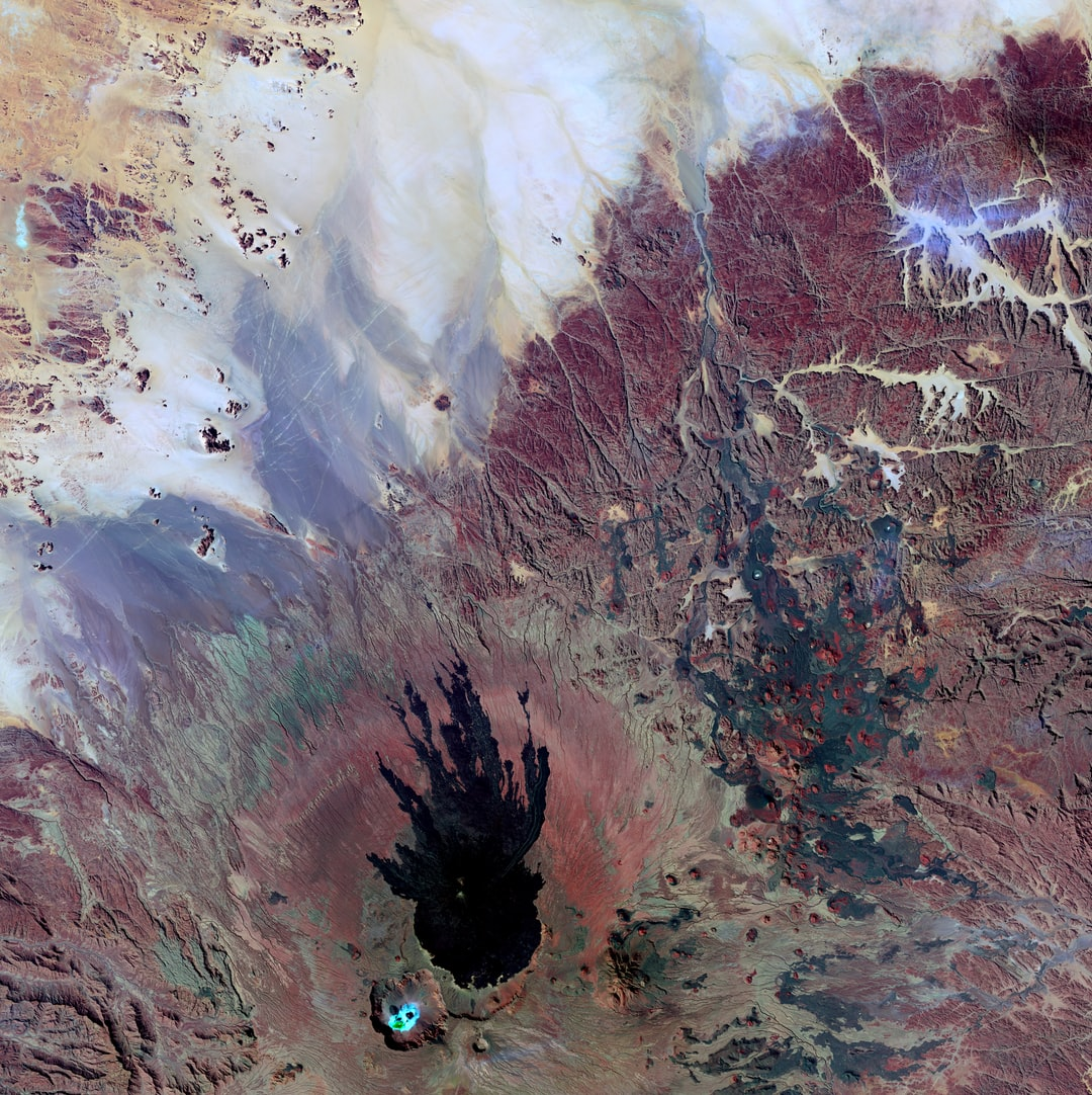 A volcanic landscape in the Tibesti Mountains of Chad shows some mysterious shapes. However, science can explain mysteries in satellite images. The octopus-shaped feature consists of ancient volcanic flows. In the crater below it, what looks like a face is bright salt deposits.